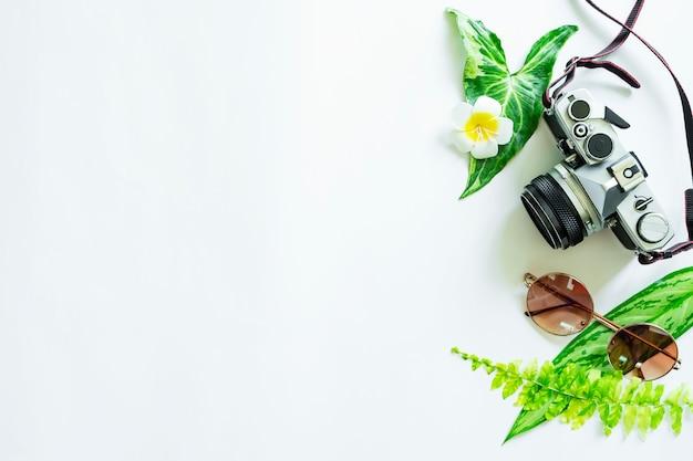 Câmera, óculos escuros e folhas verdes na mesa branca com espaço livre