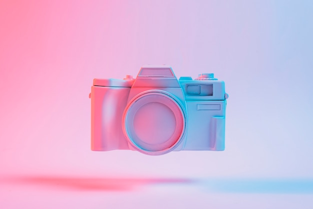 Câmera pintada flutuando com sombra contra o pano de fundo rosa