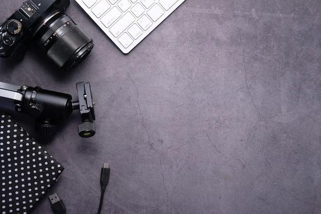 Câmera plana leiga e equipamentos na mesa de trabalho.