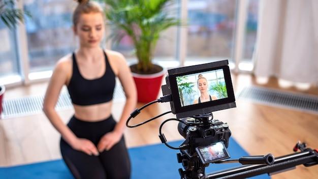 Câmera profissional com visor externo gravando uma jovem loira em roupas esportivas