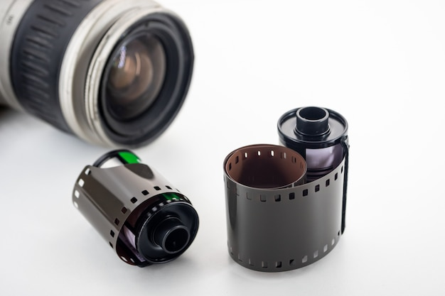Câmera reflex de lente única e rolos de filme sobre um fundo branco.