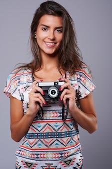 Câmera retro carregada por uma morena charmosa