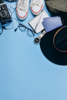 Câmera retro, chapéu, mochila, óculos, relógio, caneta, passaporte, sapatos e o bloco de notas.