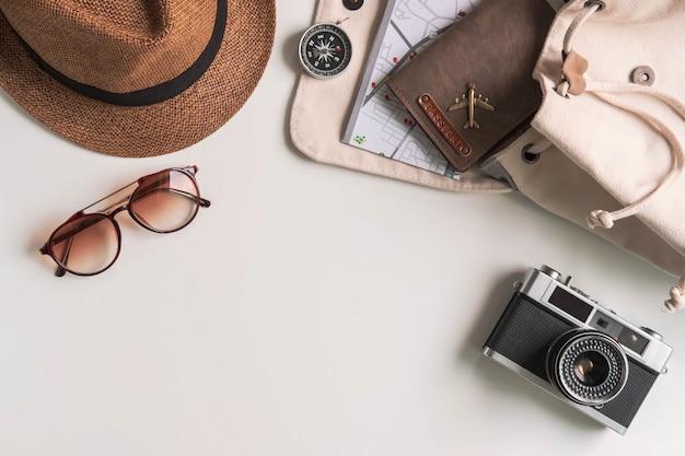 Câmera retro com acessórios de viagem e itens em fundo branco, com espaço de cópia, conceito de viagens