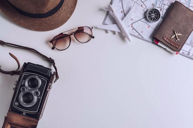 Câmera retro com acessórios de viagem e itens em fundo branco, com espaço de cópia