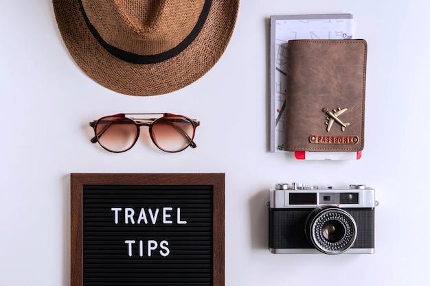 Câmera retro com avião de brinquedo, mapa e passaporte em fundo branco, conceito de dicas de viagem
