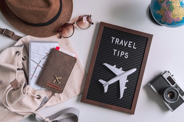Câmera retro com avião de brinquedo, mapa e passaporte em fundo branco