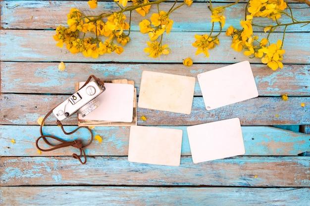 Câmera retro e álbum de fotos de papel instantâneo velho vazio na mesa de madeira com flores.