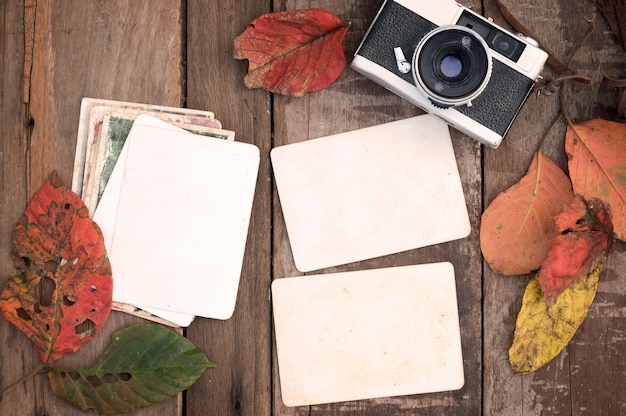 Câmera retro e álbum de fotos de papel instantâneo velho vazio na mesa de madeira com folhas de bordo no design de borda de outono - conceito de lembrança e nostalgia no outono. estilo rústico vintage.