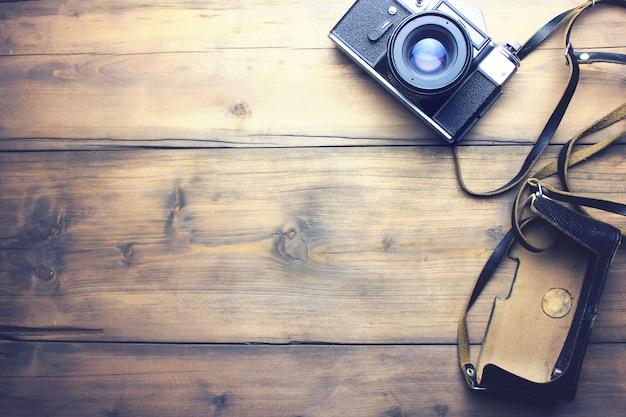 Câmera retro e bolsa na mesa de madeira
