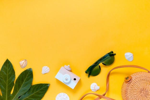 Câmera retro e óculos de sol em um fundo amarelo