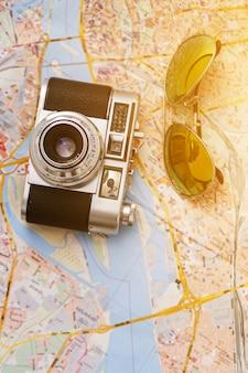 Câmera retro e óculos de sol em um mapa