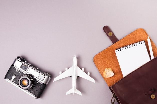 Câmera retro perto de avião de brinquedo e caso com notebook