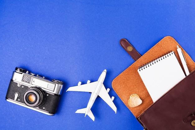 Câmera retro perto de avião de brinquedo e caso com o bloco de notas