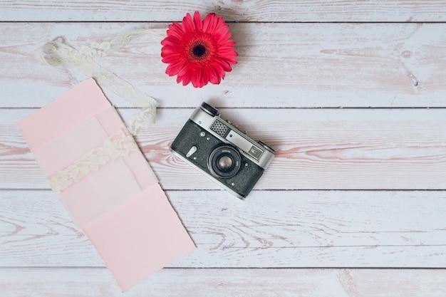 Câmera retro perto de conjunto de papéis e flores frescas