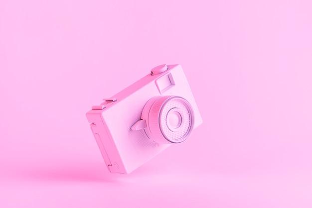 Câmera retro pintada contra fundo rosa