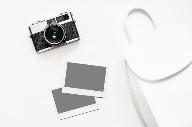 Câmera retro vintage de flatlay sobre fundo branco de madeira com foto de papel instantânea vazia