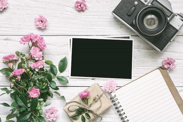 Câmera retro vintage e buquê de flores rosa rosa com moldura em branco, forrado de caderno e caixa de presente