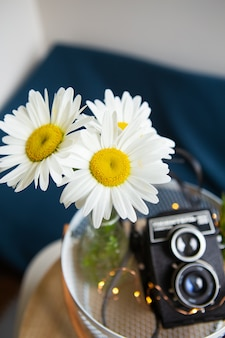 Câmera rústica vintage velha com um buquê de flores margarida em uma placa de madeira. close-up, bokeh. vista de cima.