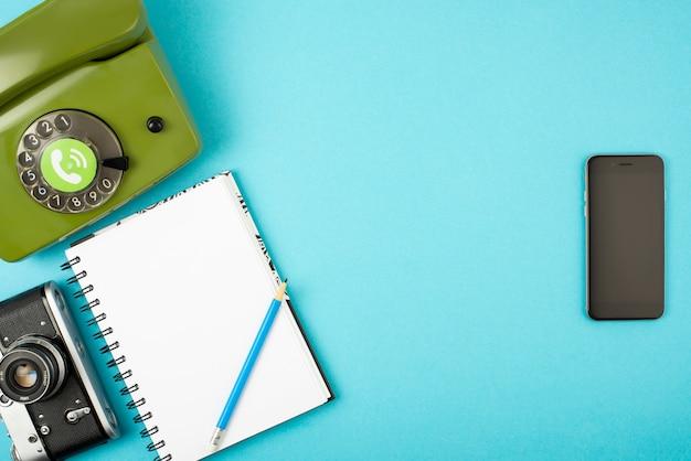 Câmera, telefone, caderno, lápis combinados em um telefone celular.