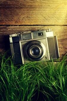 Câmera velha do vintage na grama verde com feixes luminosos no fundo de madeira. vista do topo.