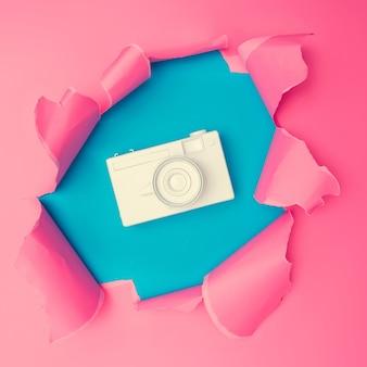 Câmera vintage branca com papel rasgado rosa vívido. fundo do buraco de estouro. conceito de papel de parede colorido abstrato mínimo.