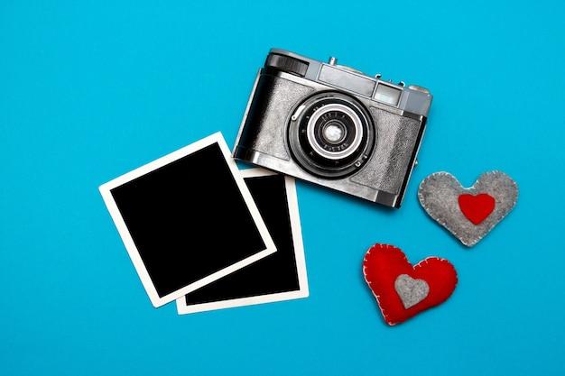 Câmera vintage com dois corações de feltro e cartões fotográficos. vista superior em fundo azul