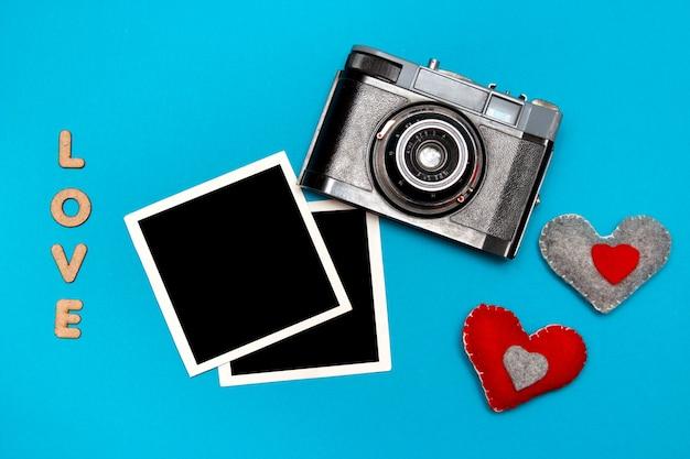 Câmera vintage com dois corações de feltro e cartões fotográficos.
