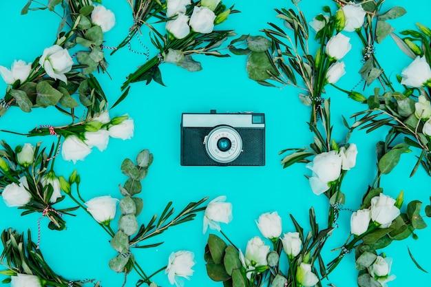 Câmera vintage com rosas brancas sobre fundo verde. acima vista