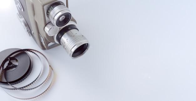 Câmera vintage de 8 mm com carretel de 8 mm em fundo branco.