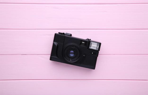 Câmera vintage em fundo rosa de madeira.