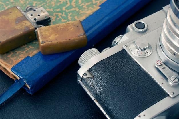Câmera vintage, isqueiro e notebook