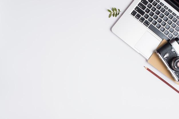 Câmera vintage; lápis; laptop aberto e galho isolado no fundo branco