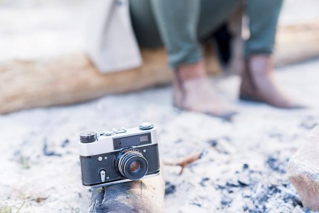 Câmera vintage no log com o viajante no fundo