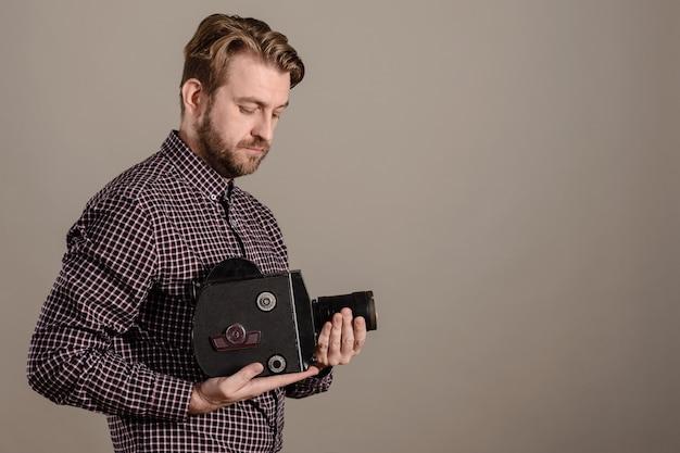 Cameraman com uma camisa xadrez segura suavemente uma câmera de filme antiga