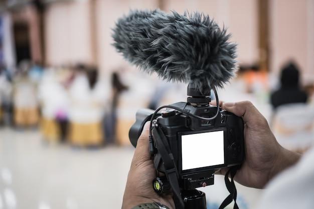 Cameraman video ou profissional digital mirrorless no tripé para gravação de câmera