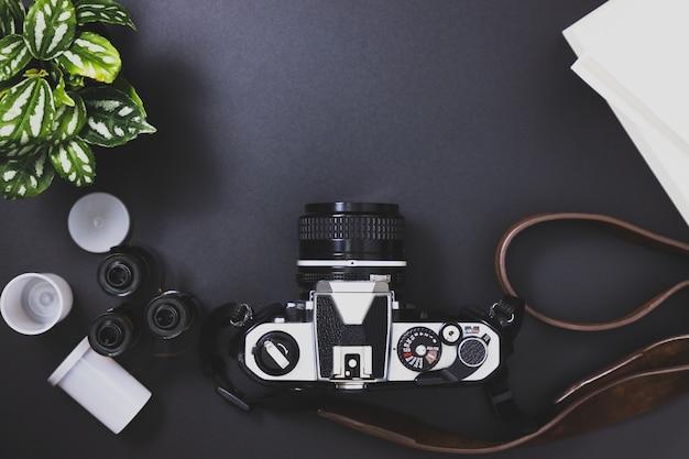 Câmeras de filme vintage e rolos de filme, livros, árvores colocadas sobre um fundo preto