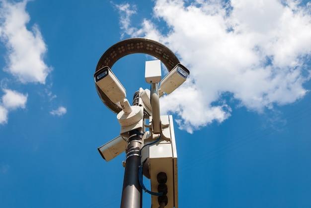 Câmeras de vigilância externas no poste com lanterna led contra o céu azul