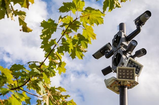 Câmeras de vigilância pretas e lâmpadas de rua brancas em uma coluna contra o céu e as folhas verdes da árvore de bordo