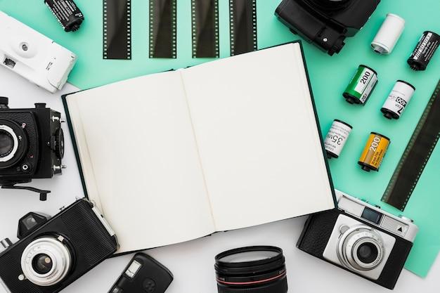 Câmeras e filme ao redor do bloco de notas aberto