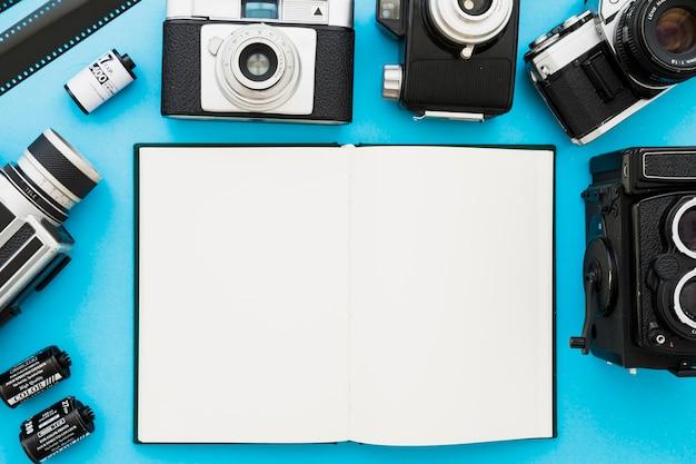 Câmeras e filme perto de caderno em branco