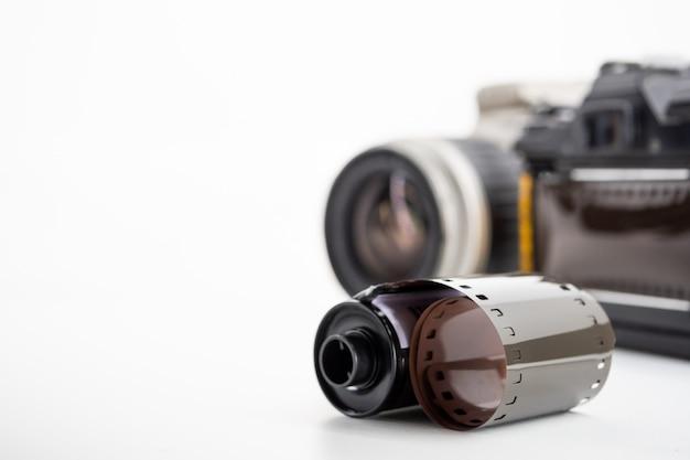 Câmeras reflex da única lente e rolos de filme em um fundo branco.