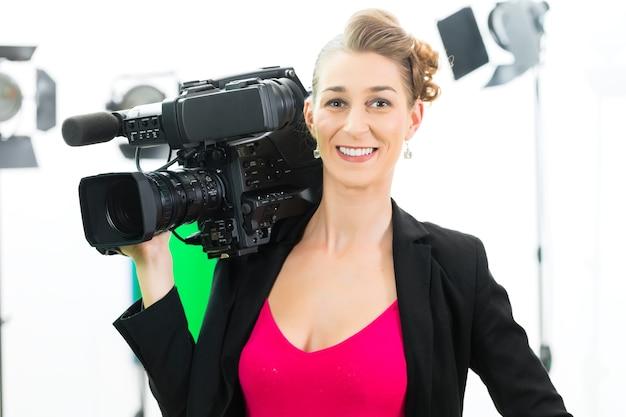 Camerawoman ou cameraman ou filmar com câmera digital em set de filmagem ou produção de vídeo para tv ou televisão ou notícias