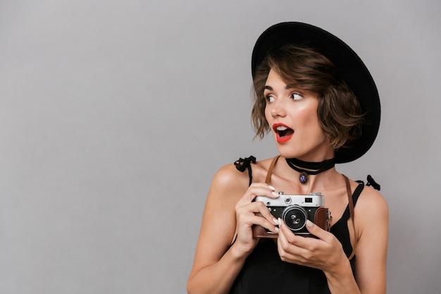 Camerawoman usando vestido preto e chapéu segurando uma câmera retro, isolada sobre uma parede cinza