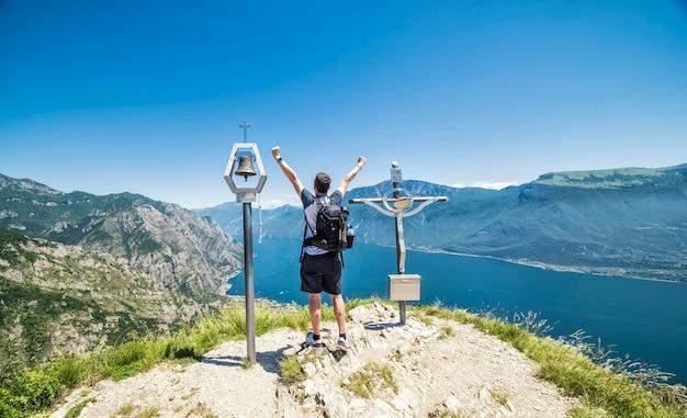 Caminhada com mochila no topo de uma montanha com as mãos levantadas e apreciando a paisagem