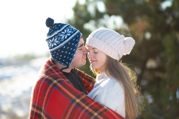 Caminhada de inverno pela floresta. o cara com a garota beijou envolto em uma manta xadrez vermelha