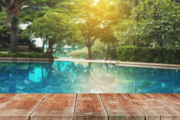 Caminhada de madeira ao ar livre na piscina residencial à terra.