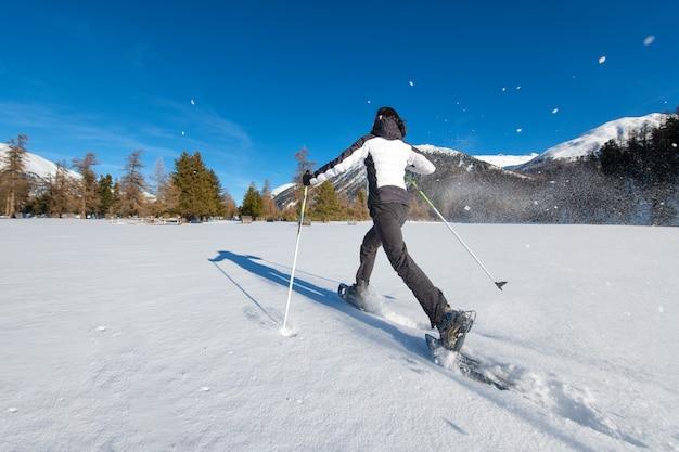 Caminhada dinâmica com raquetes de neve em uma extensão de neve