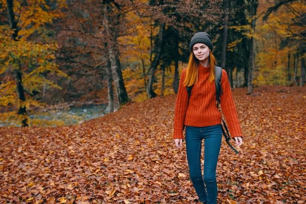 Caminhada, mulher de viagens com mochila nas costas e folhas secas caídas modelo de parque florestal natural