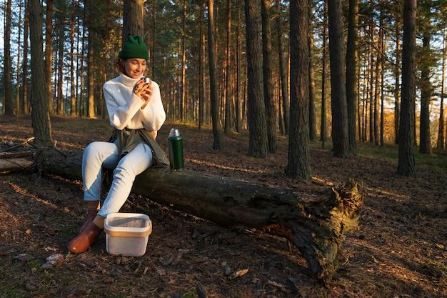 Caminhada na floresta de outono, jovem relaxando sentado em uma árvore caída bebendo uma bebida quente da garrafa térmica
